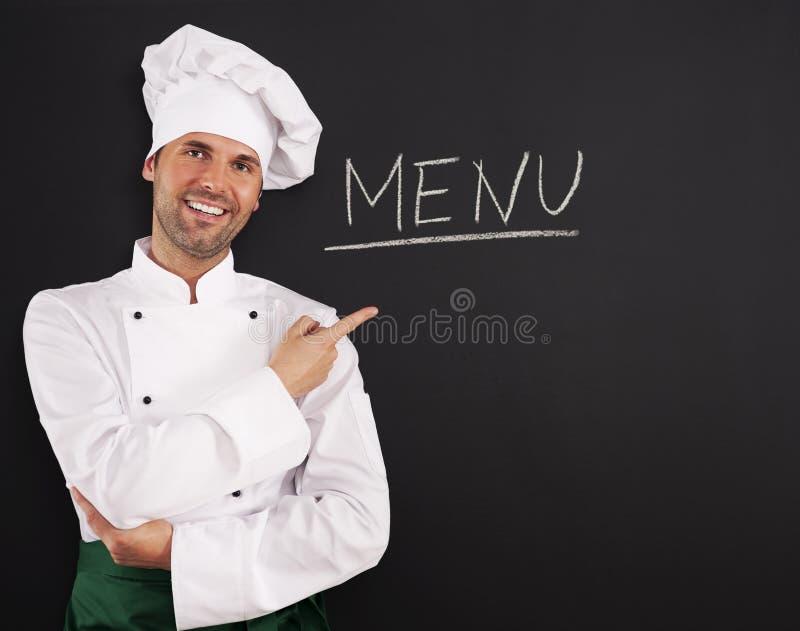 Przystojny szef kuchni pokazuje menu obraz stock