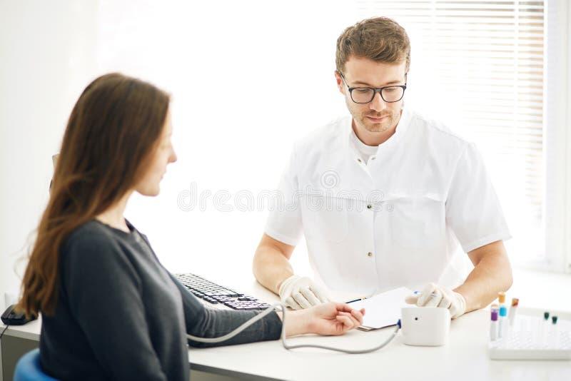 Przystojny terapeuta jest pomiarowymi kierowymi pulsami z sphygmomanometer, obraz stock