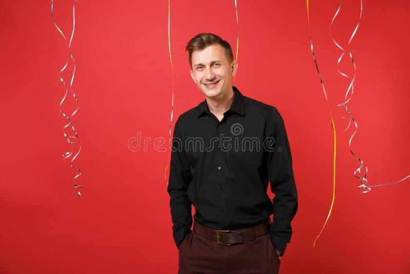 Przystojny uśmiechnięty młody człowiek w czarnej klasycznej koszulowej odświętności na jaskrawym czerwonym tle z serpentyną St wa zdjęcia royalty free