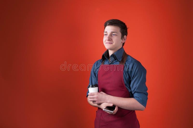 Przystojny uśmiechnięty barista z ciemnym włosy w Burgundy fartuchu trzyma papierową filiżankę i smartphone obraz royalty free