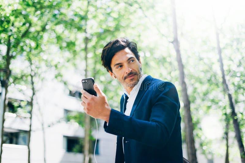 Przystojny uśmiechnięty biznesmen używa smartphone dla listining muzyki w miasto parku podczas gdy chodzący Horyzontalny, zamazan zdjęcie royalty free