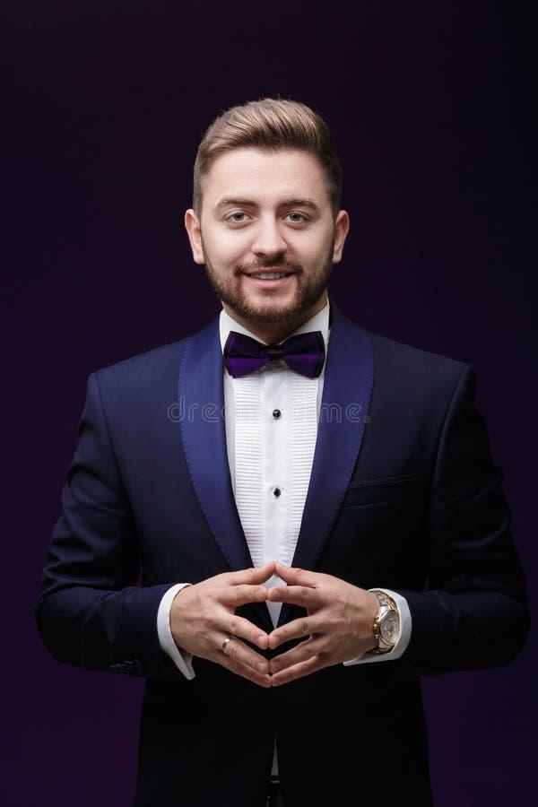 Przystojny uśmiechnięty mężczyzna patrzeje kamerę w smokingu i łęku krawacie Modna, świąteczna odzież, emcee na ciemnym tle obraz royalty free