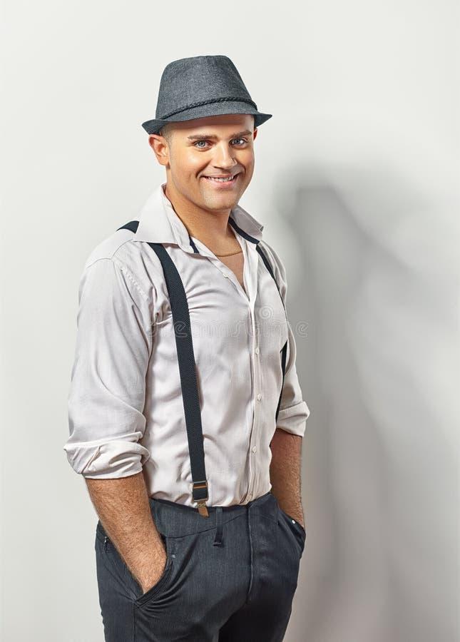 Przystojny uśmiechnięty mężczyzna w kapeluszu i suspenders zdjęcia royalty free