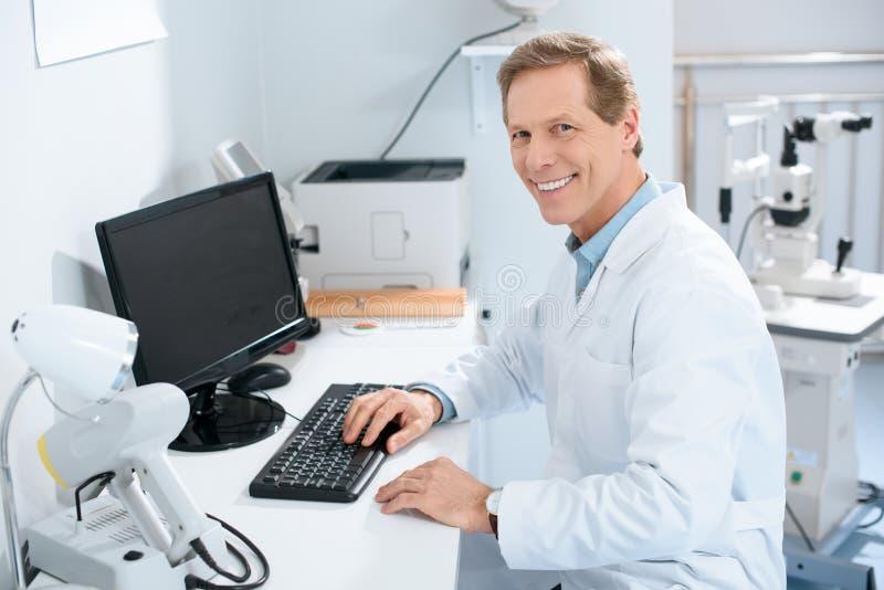 przystojny uśmiechnięty męski oftalmolog pracuje z komputerem obrazy stock