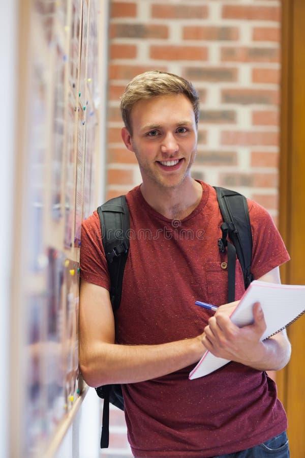 Przystojny uśmiechnięty uczeń bierze notatki obok zawiadomienie deski obraz stock
