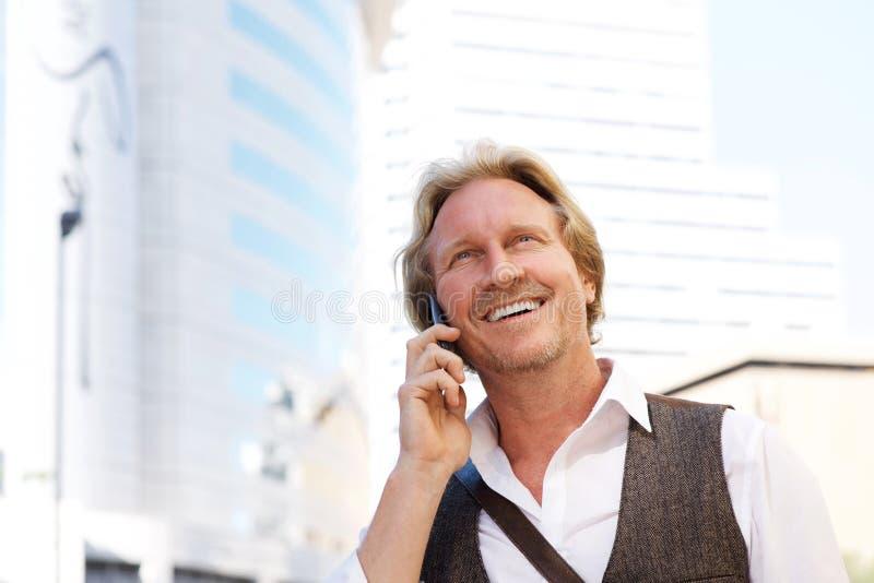 Przystojny w średnim wieku mężczyzna opowiada na telefonie komórkowym w mieście zdjęcia stock