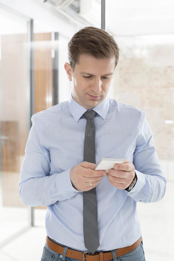 Przystojny w połowie dorosły biznesmen używa telefon komórkowego w biurze zdjęcie stock
