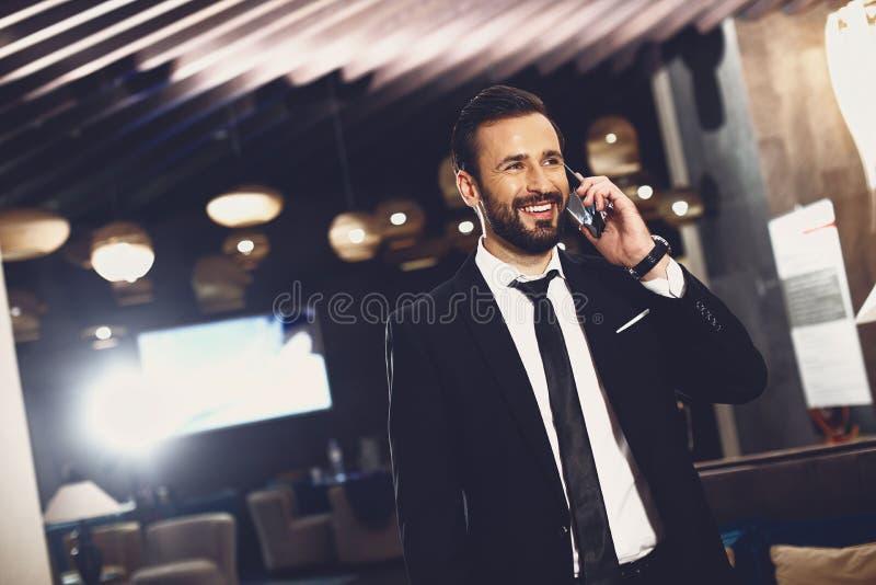Przystojny, wesoły biznesmen uśmiecha się i rozmawia przez telefon fotografia royalty free