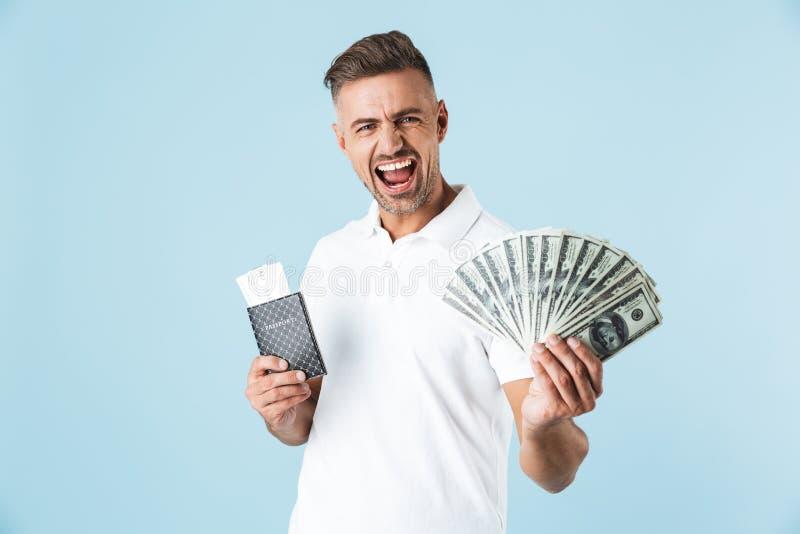 Przystojny z podnieceniem emocjonalny dorosły mężczyzny pozować odizolowywam nad błękit ściany tła mienia paszportem z biletami i obrazy stock