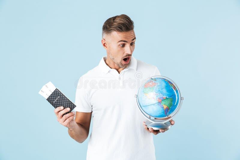 Przystojny z podnieceniem szokuję dorosły mężczyzny pozować odizolowywam nad błękit ściany tła mienia paszportem z biletami i kul zdjęcie royalty free