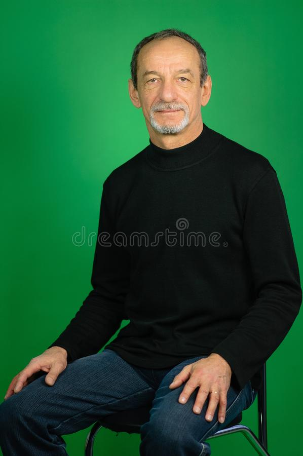 Przystojny Z włosami Dorośleć mężczyzna Siedzi na krześle na zieleni z Żyłującą brodą w Czarnym pulowerze i Ciemnych cajgach zdjęcia stock