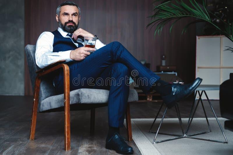 Przystojny zadumany mężczyzna dotyka jego brodę i główkowanie, patrzejący oddalony podczas gdy siedzący w karle indoors zdjęcia royalty free