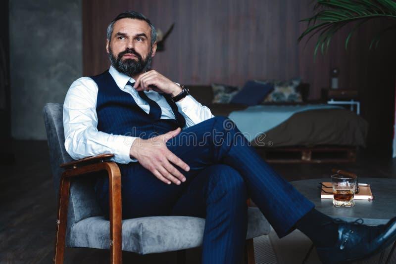 Przystojny zadumany mężczyzna dotyka jego brodę i główkowanie, patrzejący oddalony podczas gdy siedzący w karle indoors obrazy royalty free
