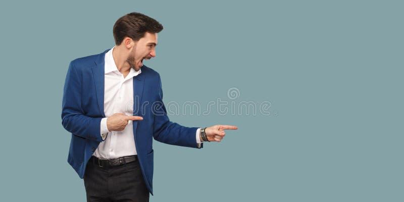 Przystojny zadziwiający brodaty mężczyzna stoi a i wskazuje w błękitnym kostiumu zdjęcia stock