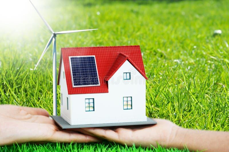 Przyszłość jest domem z photovoltaic panel i silnikiem wiatrowym zielonego, eco, zielona trawa w tle fotografia royalty free