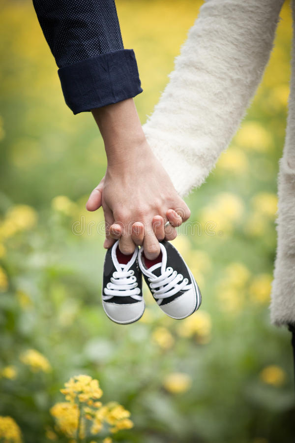 Przyszłość wychowywa mienie ręki i parę mali buty fotografia stock