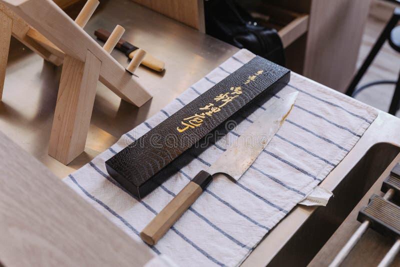 Przytępia i nieociosany Japoński kuchenny nóż czekać na ostrzenie na błękitnego paska białej tkaninie z ostrzenia wyposażeniem obrazy royalty free