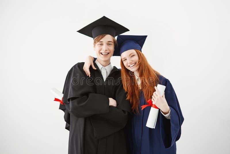 Przytłaczająca para uniwersytet kończy studia szczęśliwego otrzymywać ich dyplomy, ono uśmiecha się przy kamerą, rudzielec dziewc zdjęcie royalty free