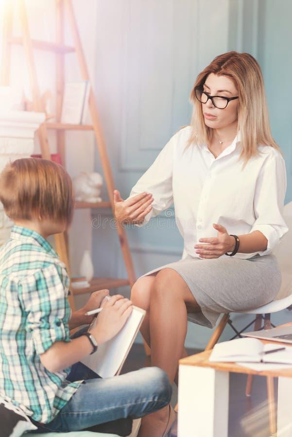 Psicólogo fêmea profissional que resolve problemas de uma estudante do adolescente imagens de stock royalty free