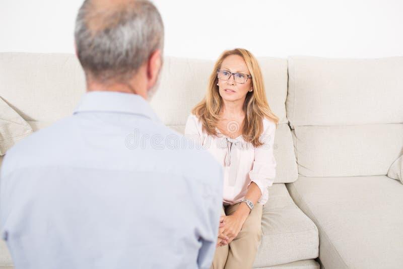 Psicólogo fêmea que escuta o homem idoso fotos de stock