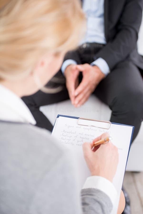 Psicólogo fêmea que faz anotações durante foto de stock royalty free