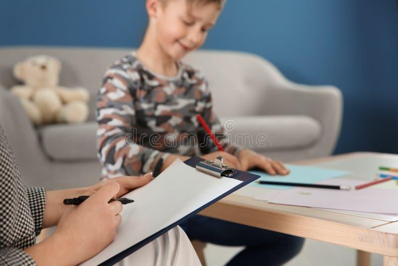 Psicólogo fêmea que trabalha com rapaz pequeno bonito imagem de stock royalty free
