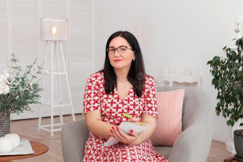 Psicólogo moreno bonito do doutor da mulher com os vidros que sentam-se em um escritório brilhante que sorri e que escreve no pap fotografia de stock royalty free