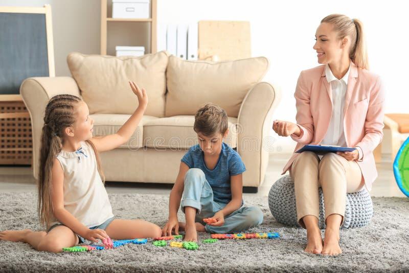 Psicólogo novo que trabalha com as crianças bonitos no escritório imagens de stock royalty free
