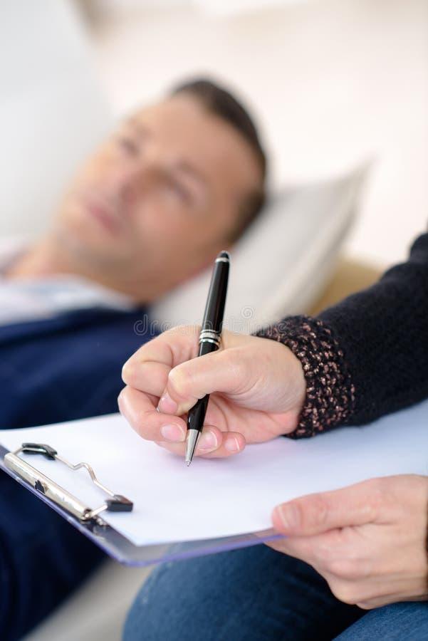 Psicólogo profissional que faz anotações na sessão de terapia fotos de stock
