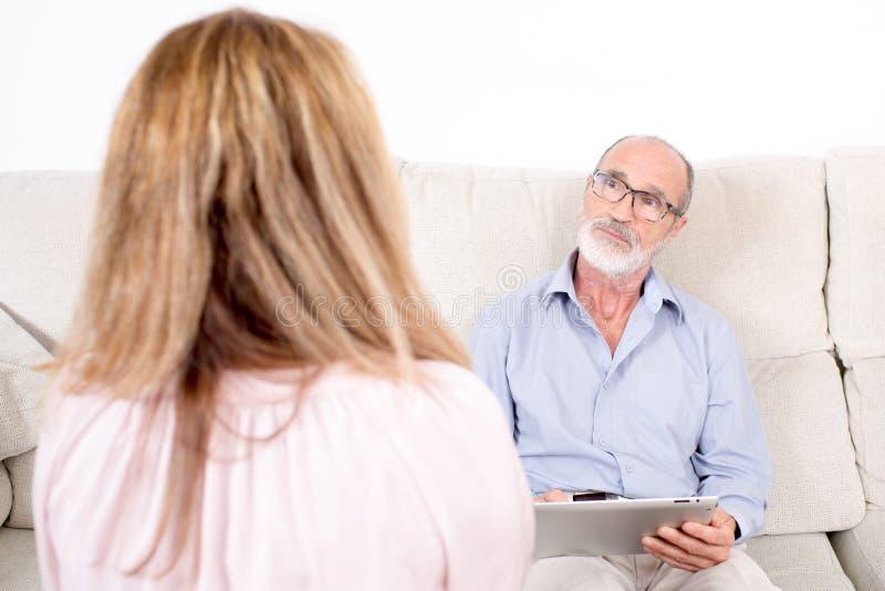 Psicólogo que escuta a mulher idosa imagem de stock royalty free