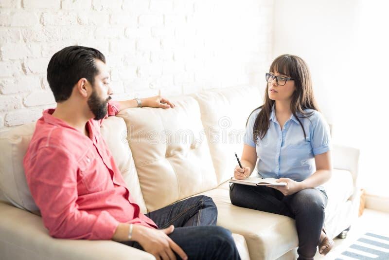 Psicólogo que fala com o homem deprimido no escritório imagem de stock royalty free