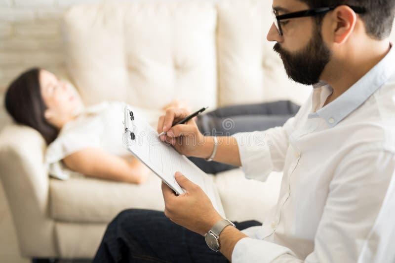 Psicólogo que faz anotações durante uma sessão da psicoterapia foto de stock royalty free