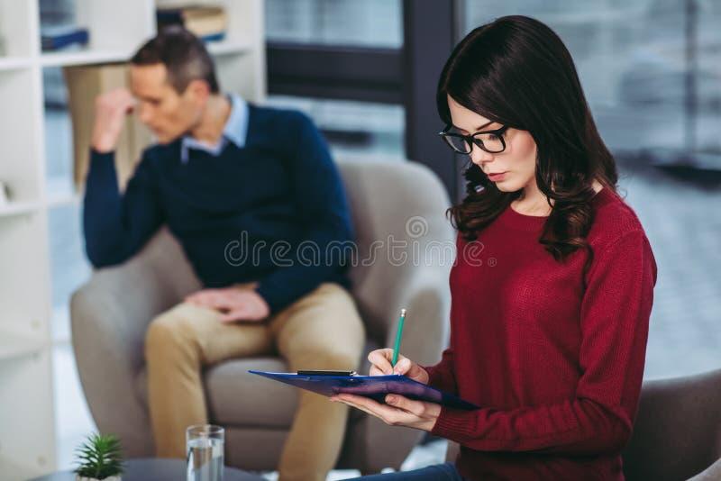 Psicólogo que hace notas en el documento imagen de archivo libre de regalías