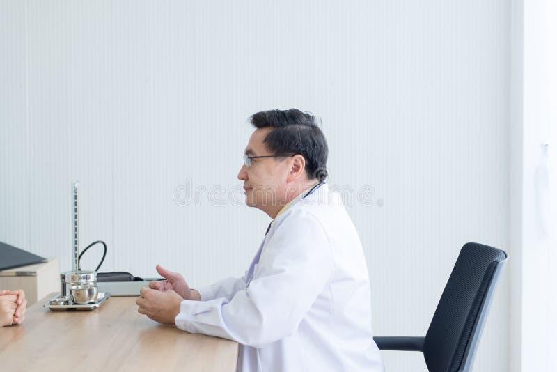 Psicólogo superior do doutor que examina e para continuar o tratamento ao paciente no hospital imagens de stock royalty free