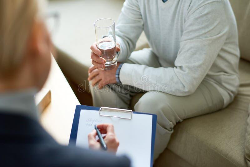 Psicólogo Taking Notes na reunião foto de stock