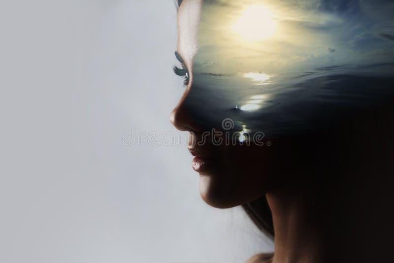 Psicanálise e meditação, conceito Perfil de uma jovem mulher e de um por do sol sobre o oceano, a calma e a saúde mental fotografia de stock