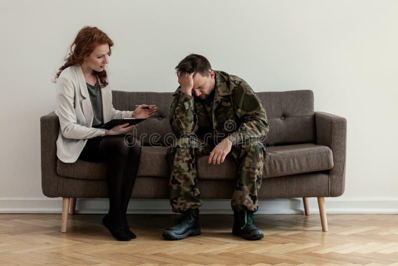 Psichiatra professionista che sostiene soldato infelice durante la consultazione fotografie stock