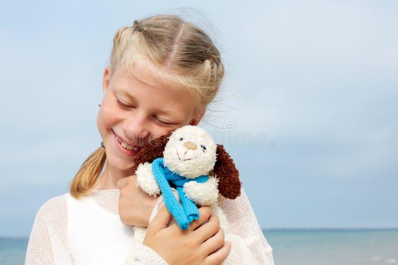 Psicología de niños La pequeña muchacha hermosa abraza un amusi fotografía de archivo