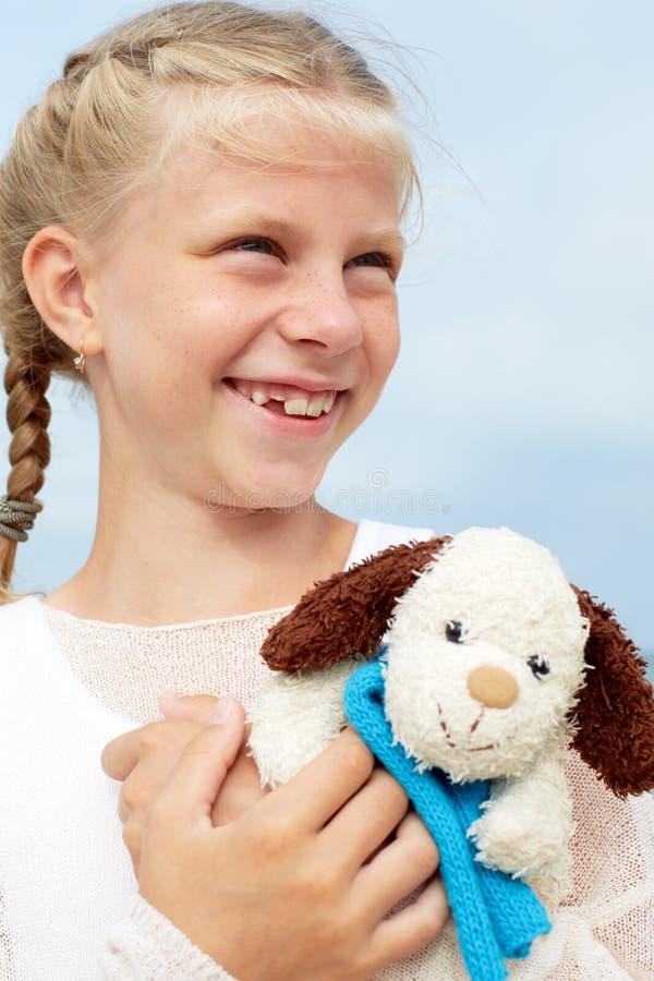 Psicología de niños La pequeña muchacha hermosa abraza un amusi fotografía de archivo libre de regalías