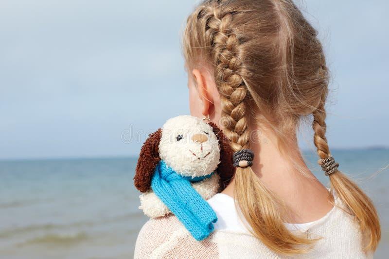 Psicología de niños La pequeña muchacha hermosa abraza un amusi imágenes de archivo libres de regalías