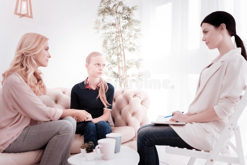 Psicologo calmo che esamina due parenti mentre consultandoli fotografia stock libera da diritti