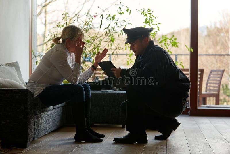 Psicologo della polizia che parla con vittime dopo il furto con scasso fotografia stock