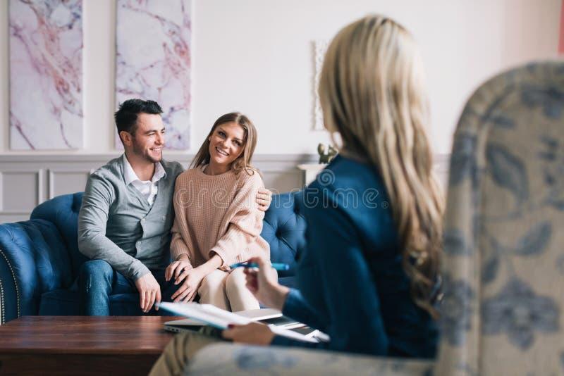 Psicologo di visita delle belle e giovani coppie felici per il consiglio di relazione immagine stock libera da diritti