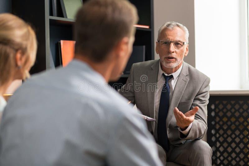 psicoterapeuta apuesto profesional confiado Gris-cabelludo que consulta a la pareja de matrimonios foto de archivo