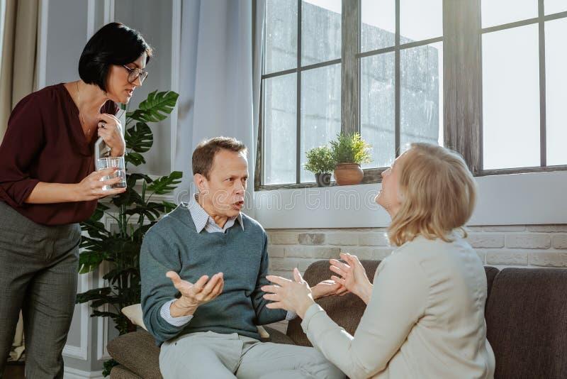 psicoterapeuta confuso Oscuro-cabelludo que propone el vidrio de agua clara fotografía de archivo