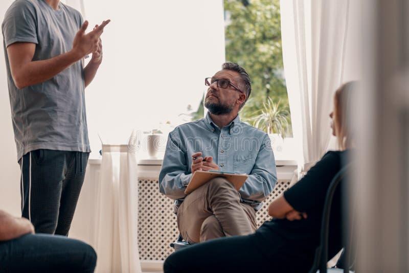 Psicoterapeuta que escucha su confesión paciente del ` s durante gro imagen de archivo