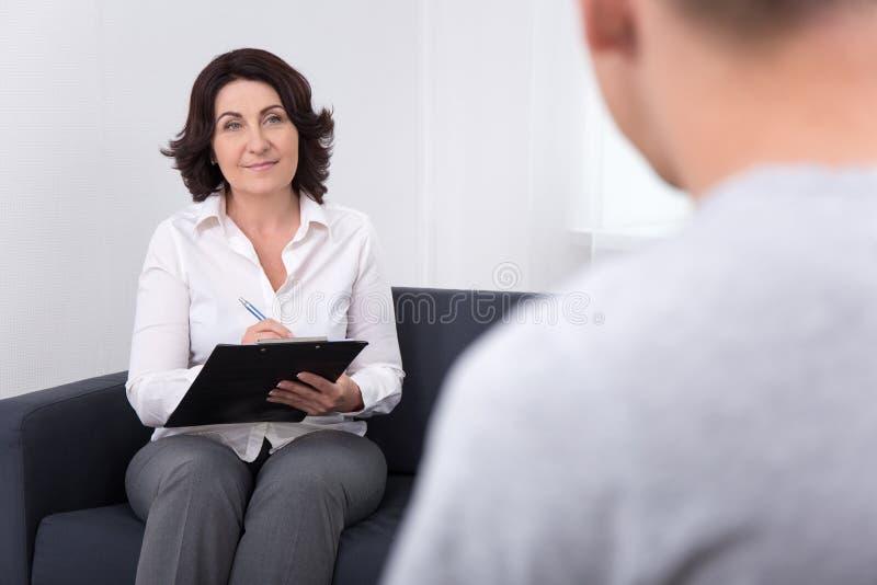 Psiquiatra de sexo femenino amistoso que examina a su paciente en oficina fotografía de archivo libre de regalías