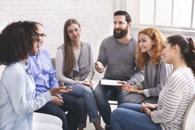 Psiquiatra del hombre que habla con los pacientes en la reunión de grupo de la rehabilitación imagenes de archivo