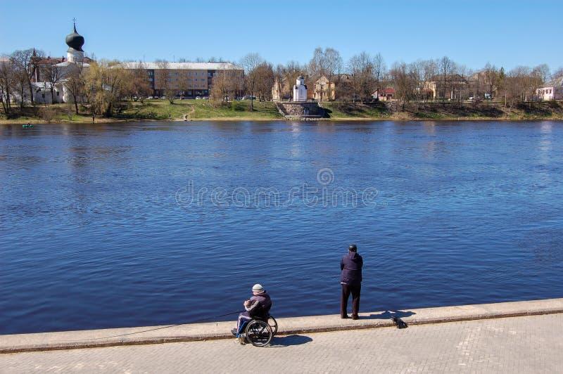 Pskov, Rússia 04 pode 2017 Um homem em uma pesca da cadeira de rodas Pescadores numerosos no rio de Velikaya perto do Kremlin fotografia de stock