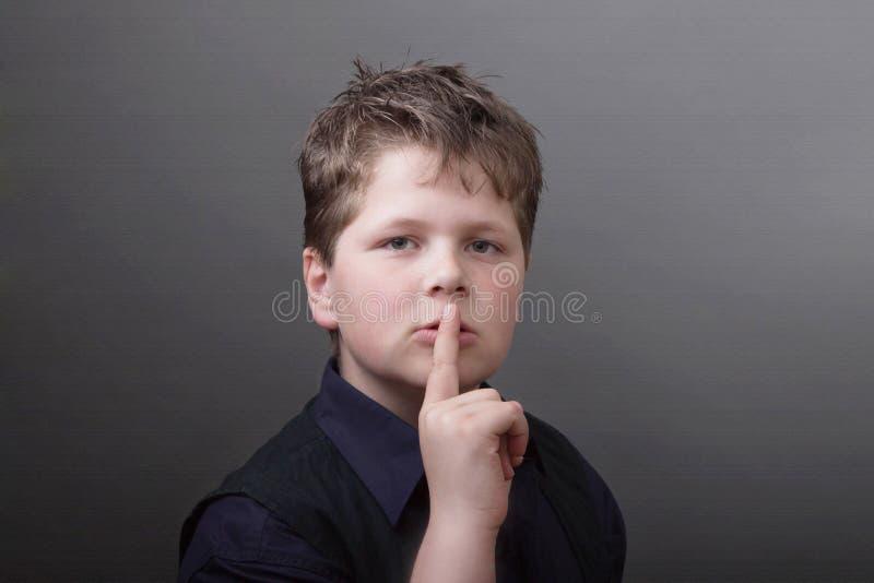 Psst… zadawala był spokojny. Chłopiec z cisza znakiem zdjęcie royalty free
